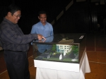 Judge Candelario Gonzales, SAAI president, admires the scale model of the projected Portal West building